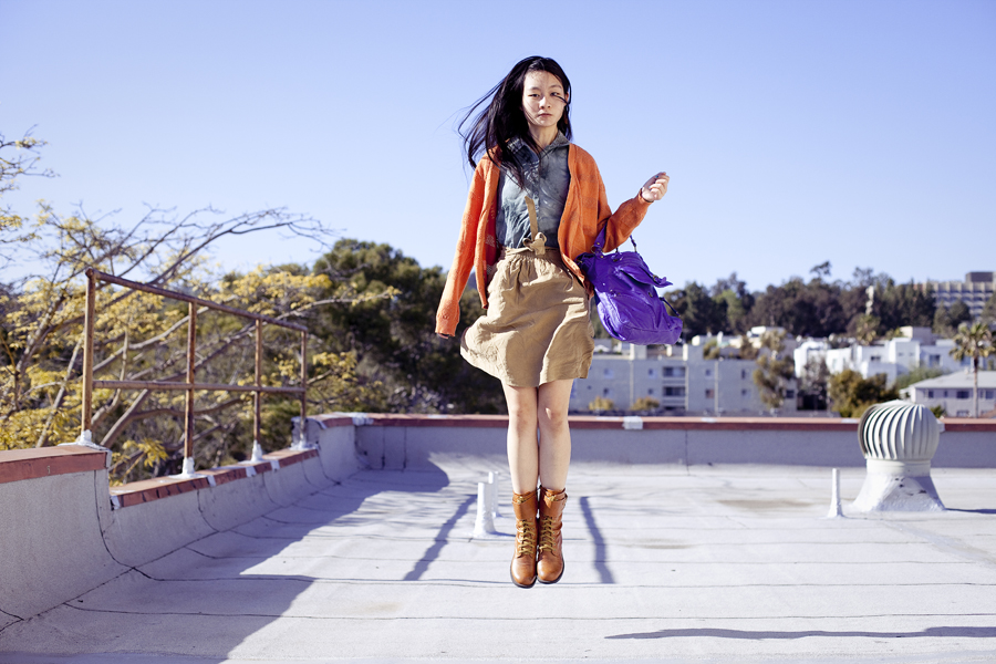 Rooftop jumping photoshoot. Wearing Urban Outfitters dyed sleeveless top with studded collar, Forever 21 orange perforated boyfriend cardigan, Zara brown front-tie skirt with pockets, green crocodile socks, Top Shoes brown zippered boots, T-shirt & Jeans leatherette purple sling bag.