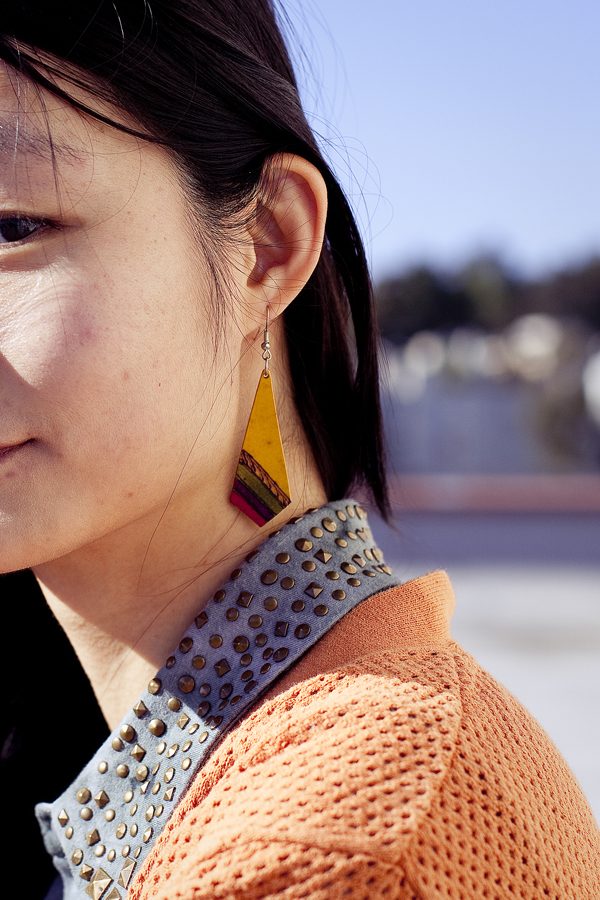 Rooftop photoshoot. Detail of Urban Outfitters dyed sleeveless top with studded collar, Forever 21 orange perforated boyfriend cardigan, yellow wooden earring handmade from a stall in Buenos Aires, Argentina.