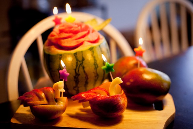 Candles on sculpted watermelon flower and swan apples.