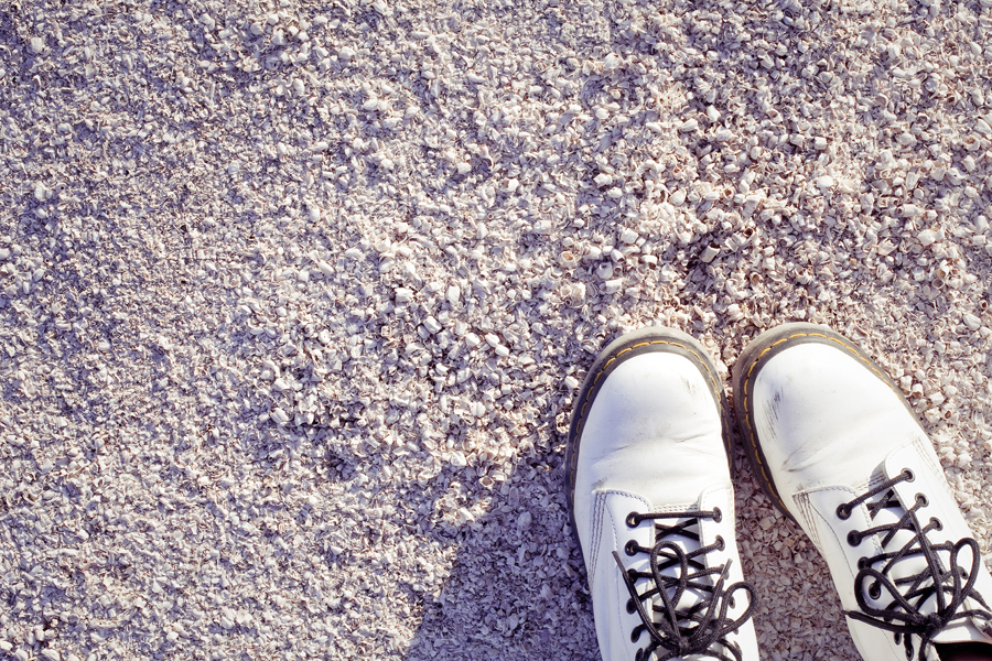 Ren's white dr martens boots on the beach by the Salton Sea.