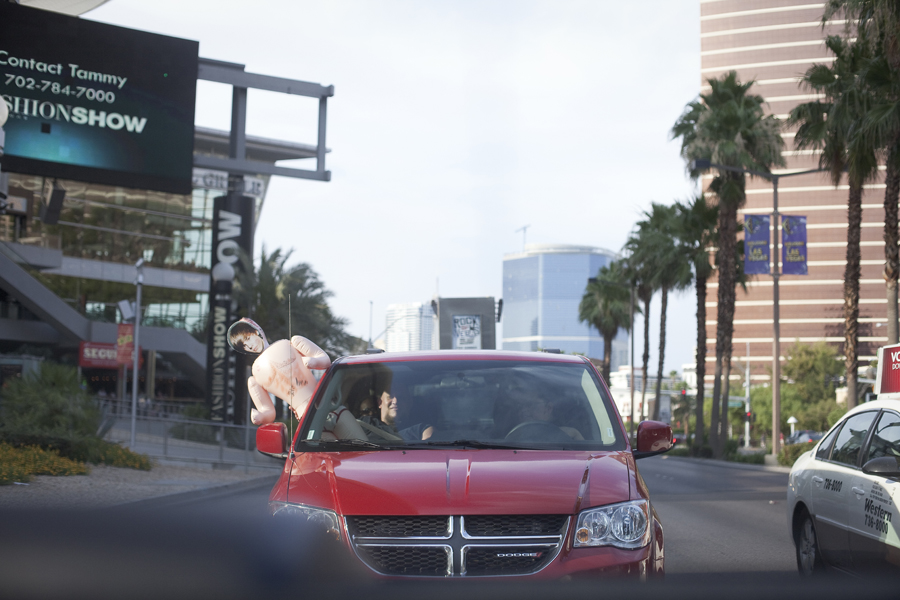 Justin Bieber face on a blow up doll hanging out of a car for his concert in Las Vegas.