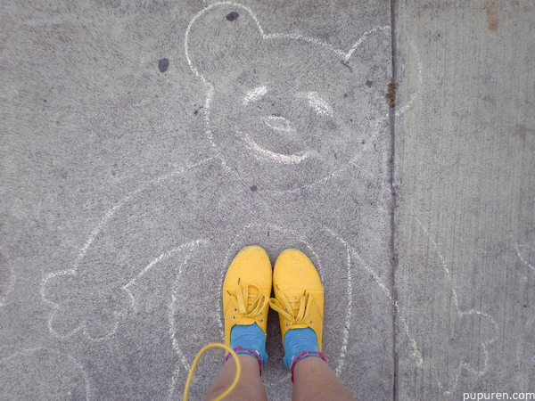 Chalk drawing of a bear on the pavement.