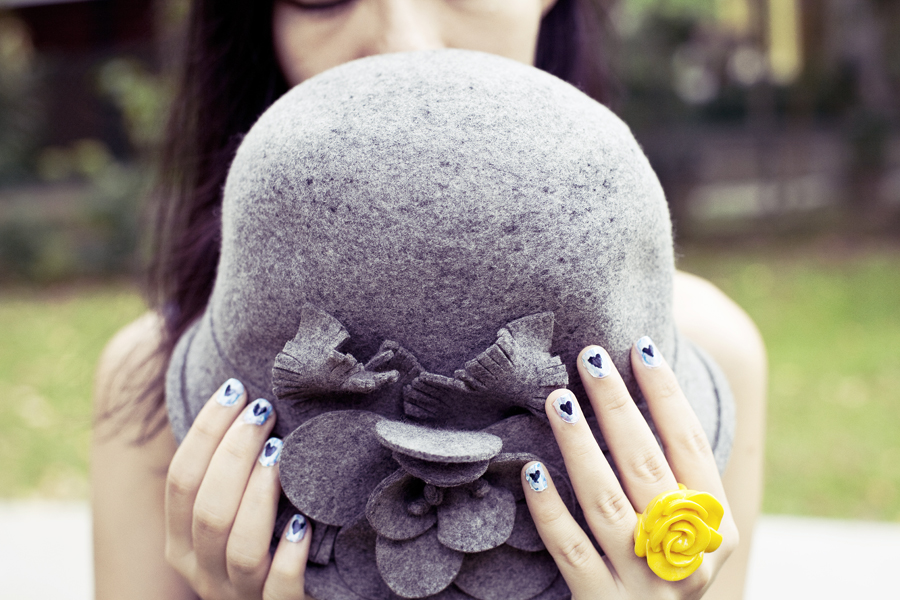 Wool hat, painted blue nails, yellow rose plastic ring.