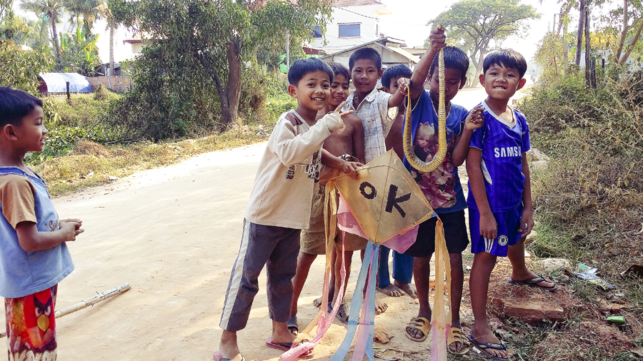 Locals kids holding up a snake and a kite outside the Lotus Lodge, Siem Reap, Cambodia.