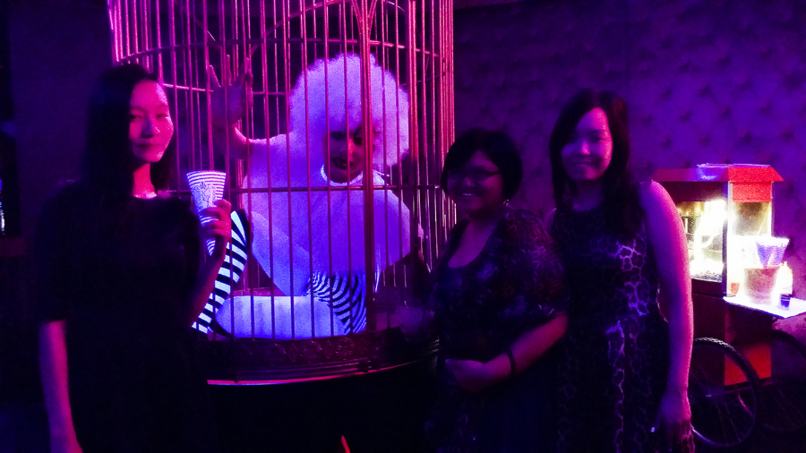 Ren, Puey, and Ade taking a picture with a performer in a cage at Cirque le Soir nightclub in Shanghai.