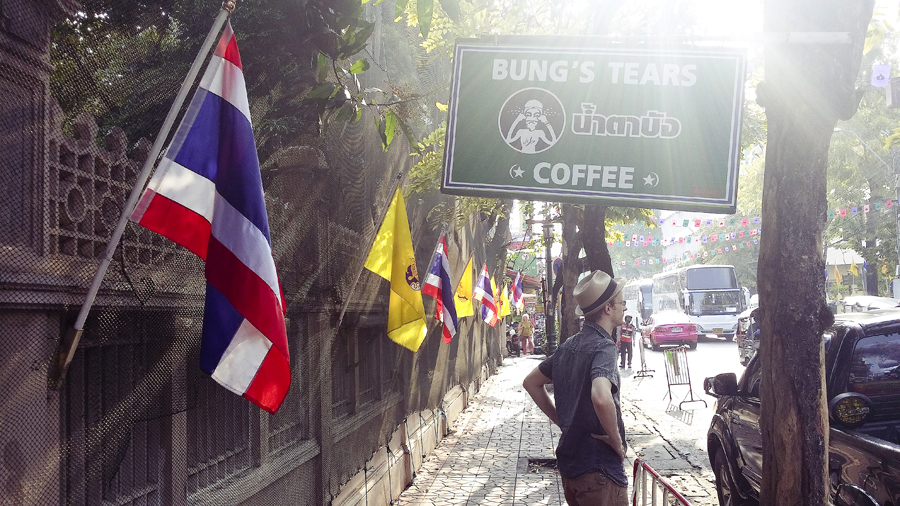 Ottie standing underneath a sign of Bung's Tears Coffee in Bangkok, Thailand.
