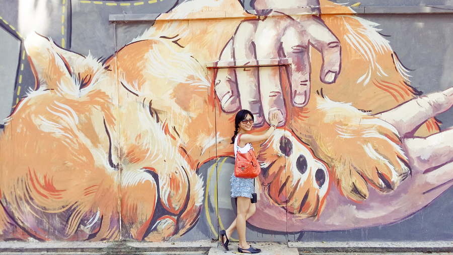 Alala posing with Girl and the Lion Cub, a mural by Ernest Zacharevic.
