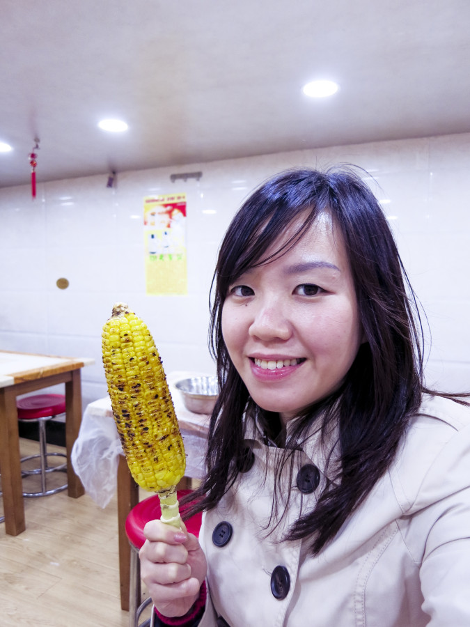 Ade posing with grilled corn in Shanghai.