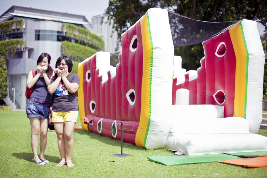 Photo of Ade and Puey posing in front of an inflatable plastic mockup of a watermelon see-saw at the Masak Masak exhibit at the National Museum of Singapore.