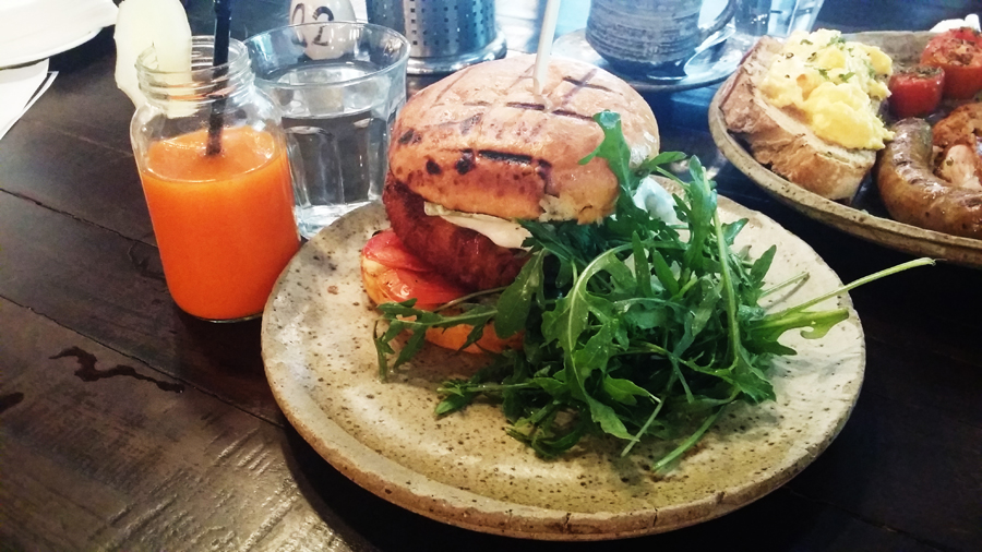 Fish Burger and a glass of Fresh orange, carrot & ginger juice from Common Man Coffee Roasters.