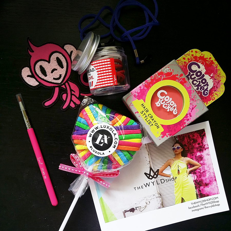 Flatlay beauty goodies: LeSpecs glasses holder, Color Bucket pink hair chalk, Luxola.com colourful hair ties in lollipop, The WYLD Shop postcard.