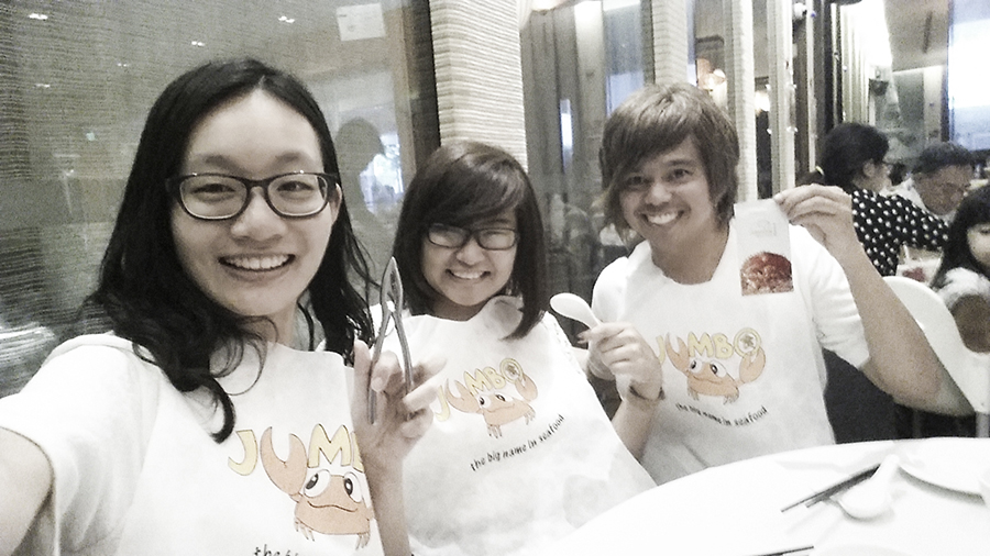 Ren, Jesca, and Shamis wearing bibs for chilli crab at Jumbo Seafood Restaurant at The Riverwalk, Singapore.