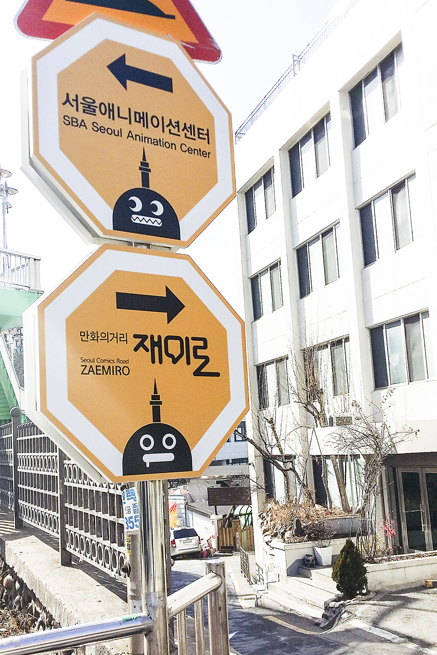 Road signs pointing to Seoul Animation Center and Zaemiro Seoul Comics Road in South Korea.