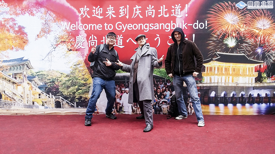 Tim, Ottie, and Ant posing in front of an event promoting Gyeongsangbuk-do in Myeongdong, Seoul, South Korea.
