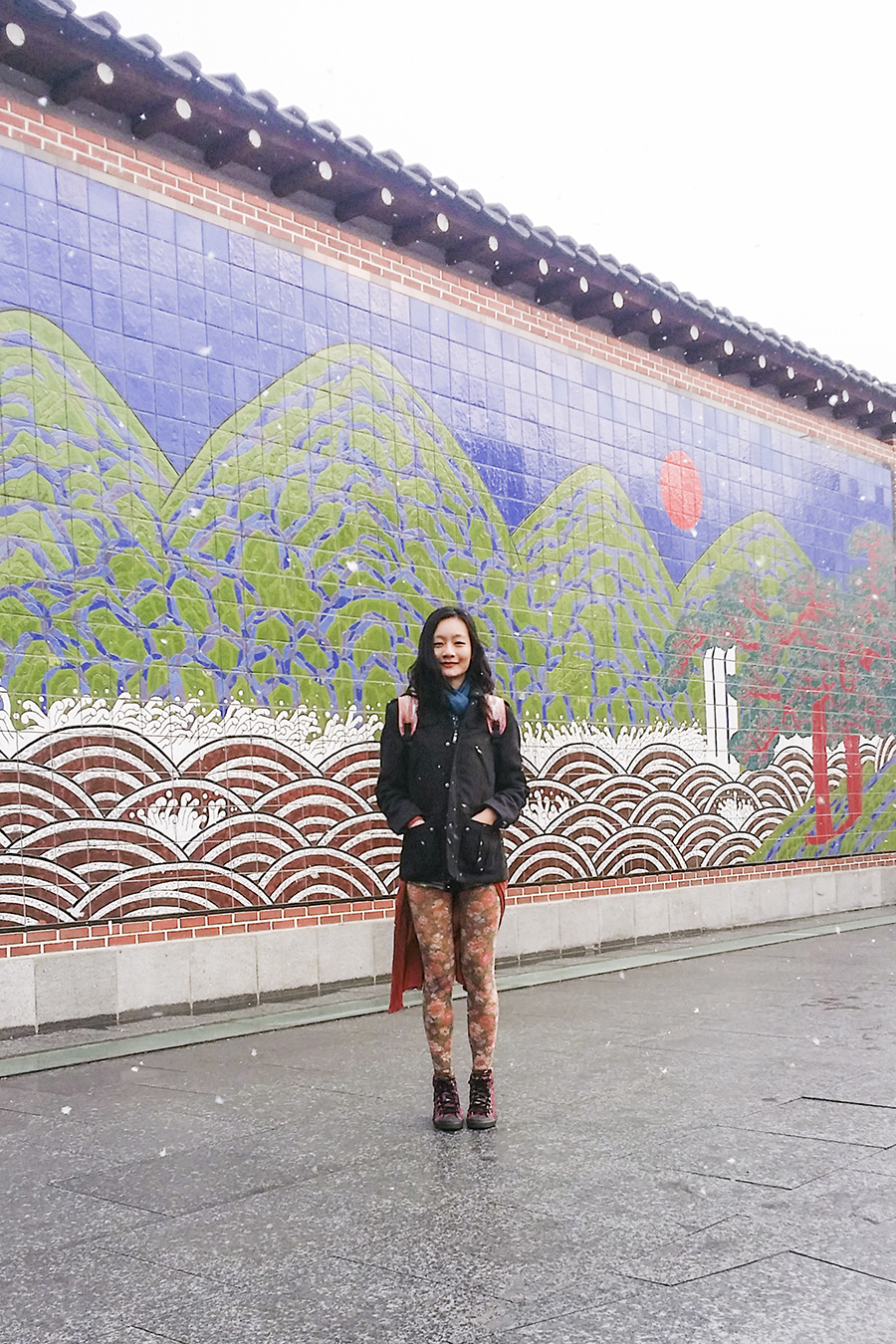 Outfit photo against a tiled wall of a landscape mosaic in Seoul, South Korea.