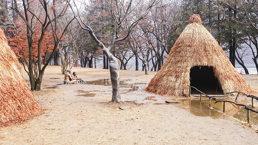 Thatched huts with sculptures of tribal humans at Nami Island, Gapyeong, South Korea.