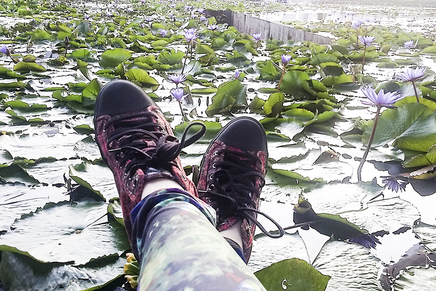 Red Rush Alexander McQueen sneakers and H&M abstract leggings against a lotus pond at Marina Bay Sands, Singapore.
