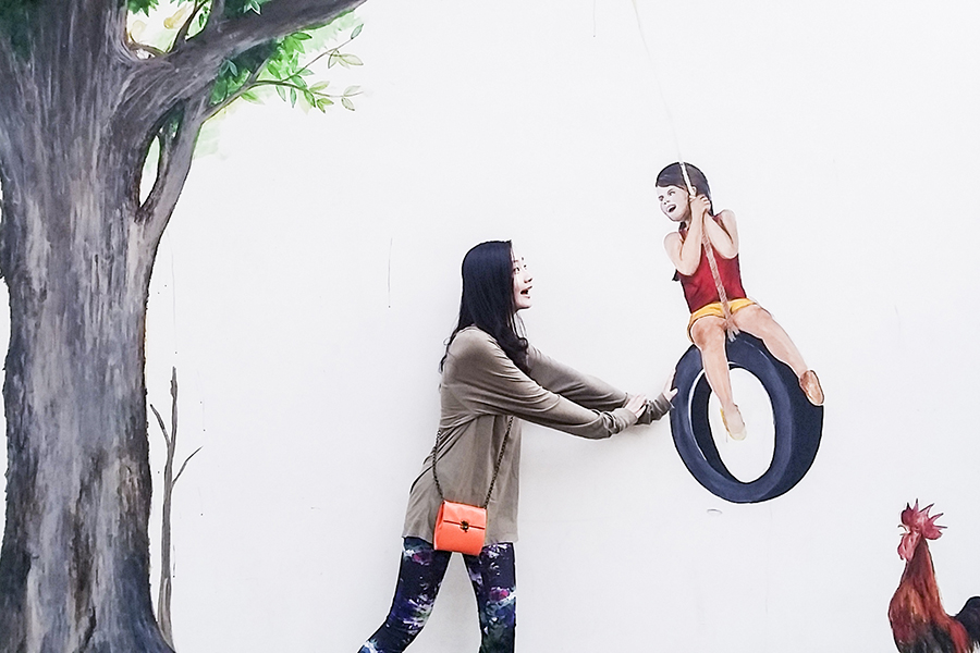Ren pushing a girl on a tire swing illustrated mural in Singapore.