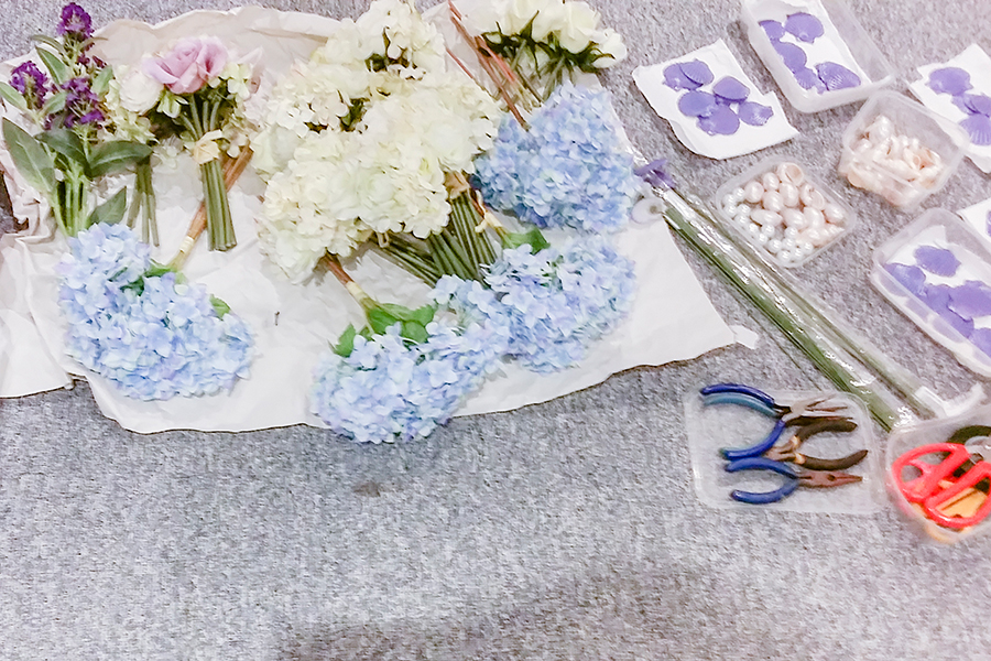 Craft materials for DIY floral wreath: artificial flowers, wire, pliers, purple seashells.