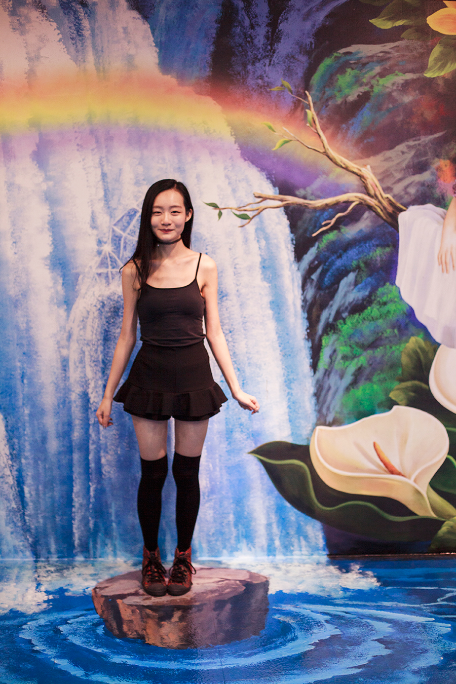 Standing on a log in front of a fairytale scene trompe-l'œil at the Trick Eye Museum Renewal Event in Singapore, Resorts World Sentosa.