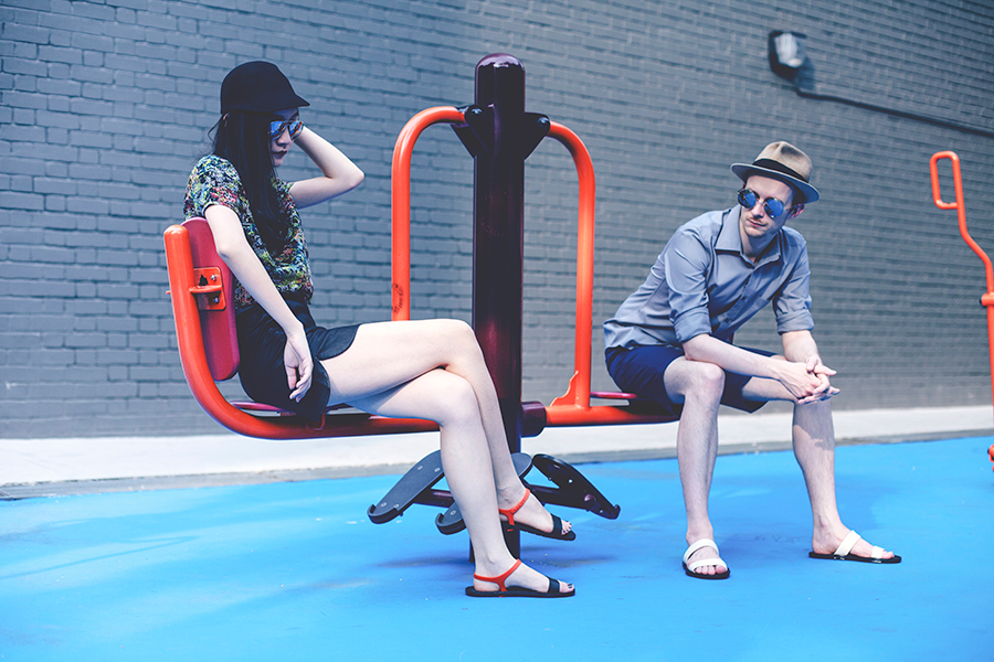 Couple modeling BlackOut sandals at the playground.