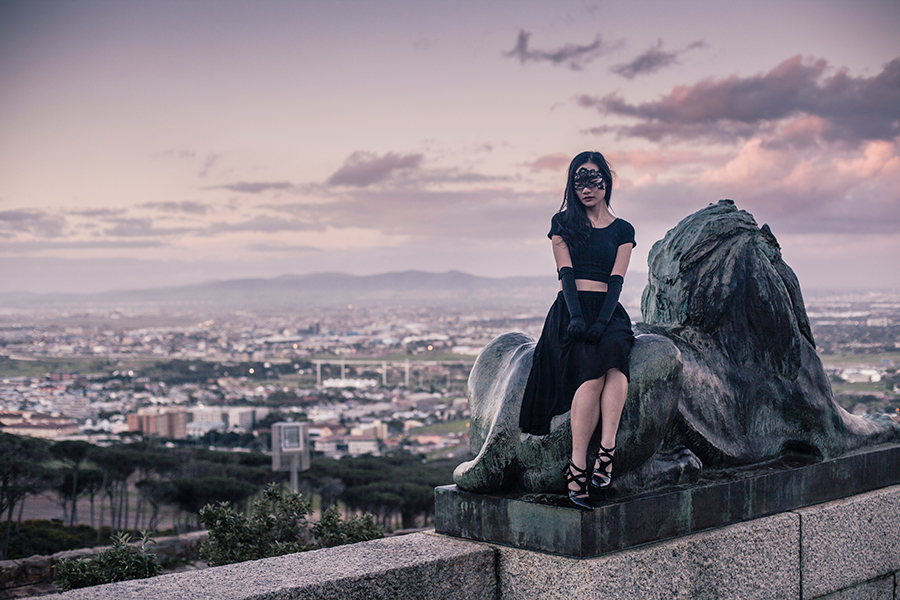 Sitting atop lion sculpture at Rhodes Memorial, Table Mountain National Park, Cape Town, South Africa.