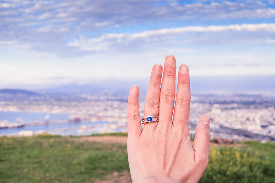 Sapphire gemstone set in platinum band engagement ring against the city of Cape Town, South Africa.