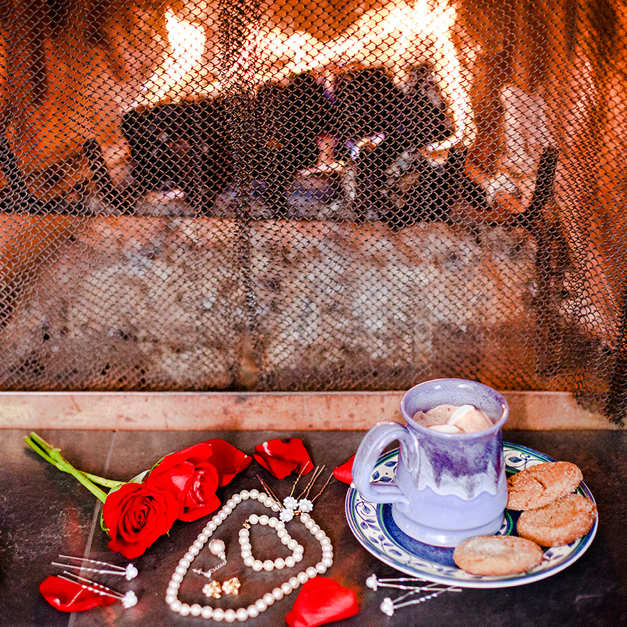 Roses, jewelry, homemade ginger snaps, and marshmallows in hot chocolate in front of a fireplace in winter.