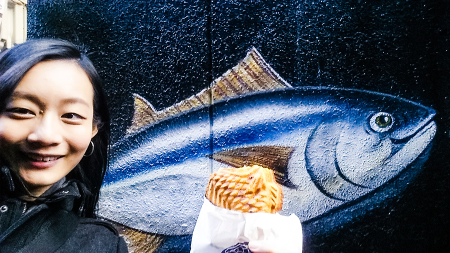 Taiyaki in front of a fish mural in Osaka, Japan.
