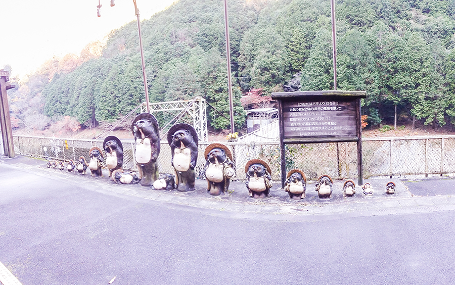 Family of tanuki statues from the Sagano Romantic Train above the Hozugawa River, Kyoto, Japan.