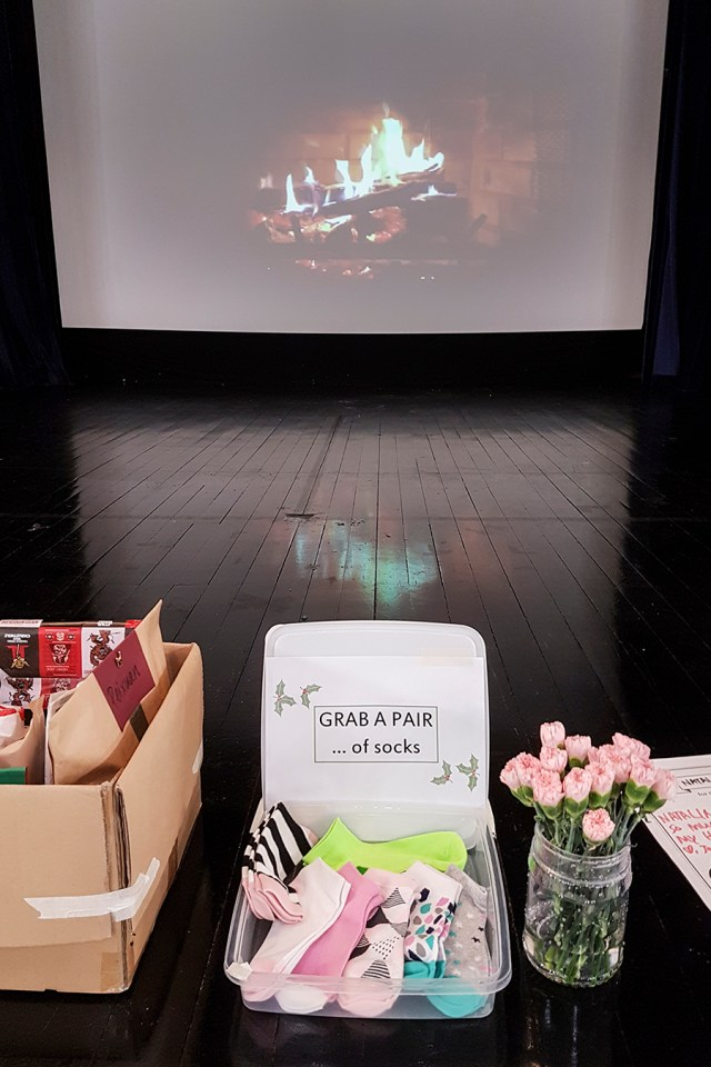 Presents and gifts for Merparty 2016 in front of a projecter screen depicting a fireplace.
