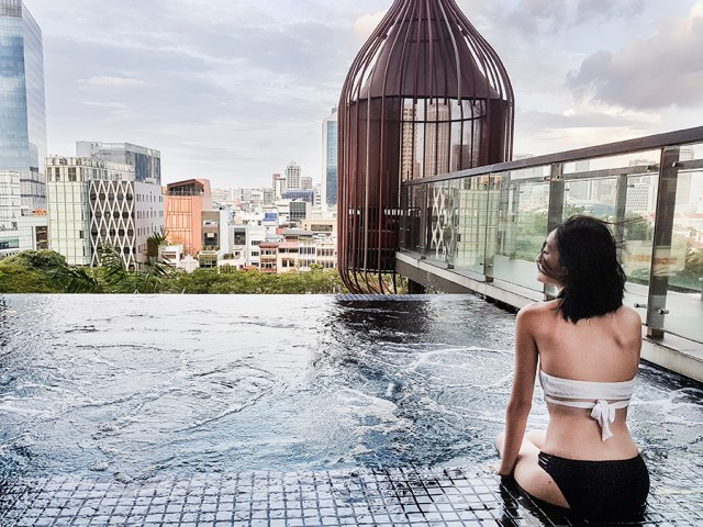 Lounging by the jets at the infinity pool at hotel PARKROYAL on Pickering, Singapore. Wearing Piha white wrap lace bikini top, Bella Kini black lace bottoms.