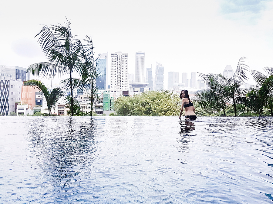 Ren by the edge of the infinity pool in Malibu Beachwear Maxim Black Neoprene Surf Tank Set at PARKROYAL on Pickering, Singapore.