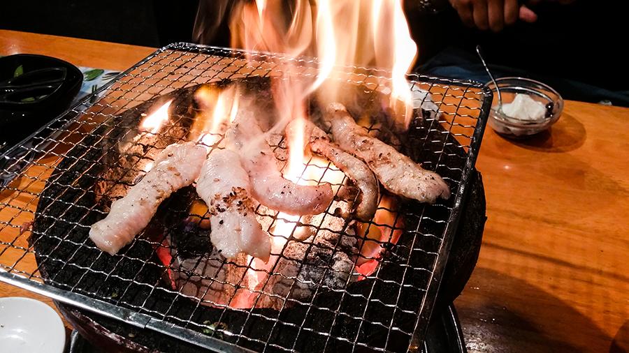 Grilling beef yakiniku at Fuu Fuu Ten in Osaka, Japan.