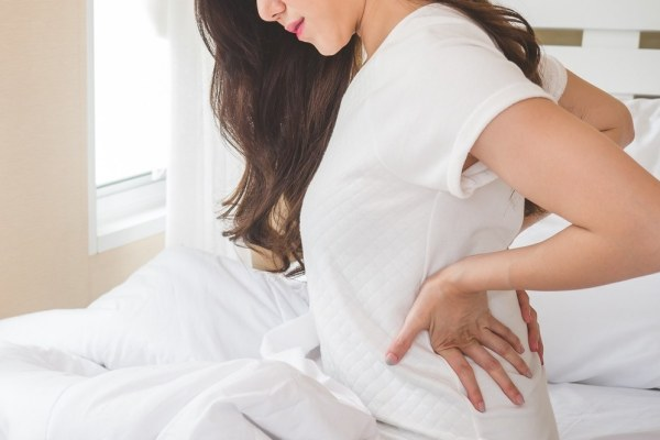 Woman sitting on bed with hands on her back