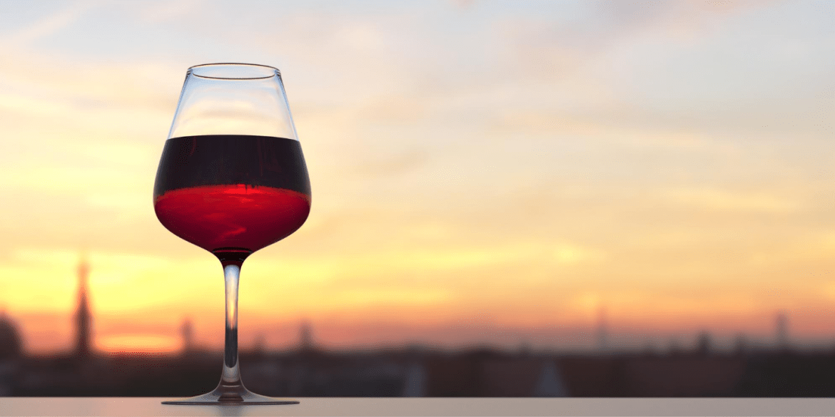 A glass of red wine with a sunset in the background. Resveratrol is a compound found in red wine.