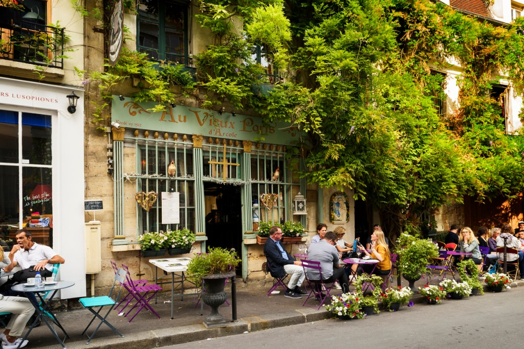 "Famous style of life in Paris, France with Bistrots and people on terraces. Here, this is ""The old Paris"" traditional Bistrot on the Ile de la Cite in the spring time, near Notre Dame."