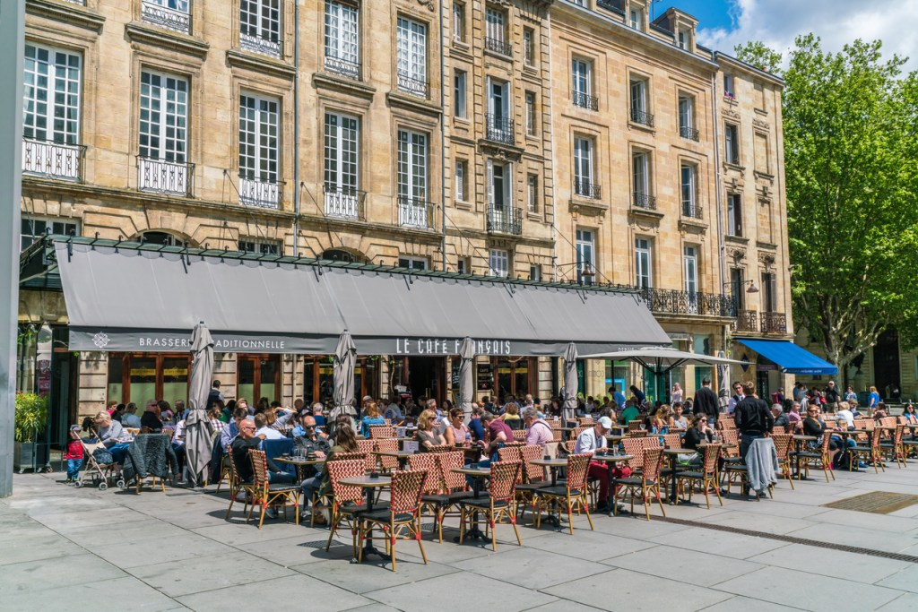 Bordeaux, France, 9 may 2019 - Locals and tourists eating and drinking on a terrace on the  'Place Pey Berland' opposite of the Famous Cathédrale Saint-André de Bordeaux