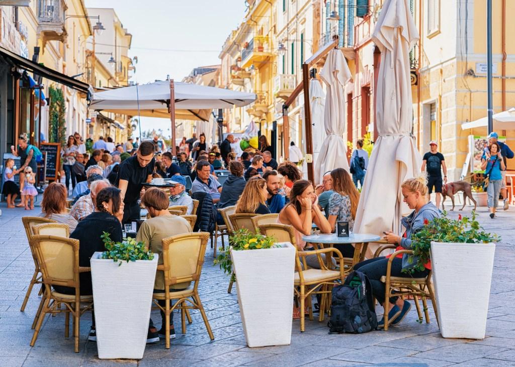 Tourists at street cafe on Corso Umberto Street in Olbia, Sardinia, Italy
