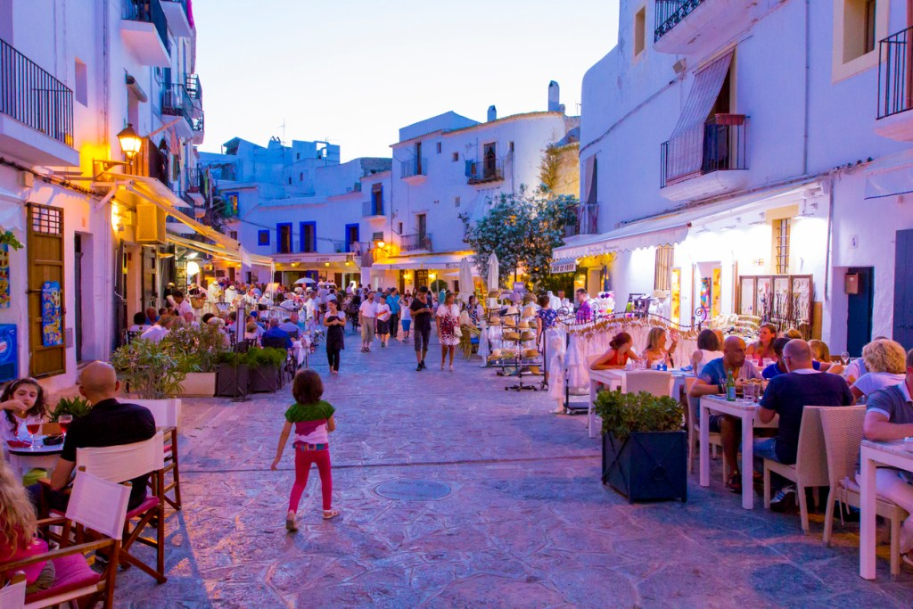 Street in old town with strolling promenade tourists and vacationers visiting street cafes and restaurants in evening light of street lamps and sunset.