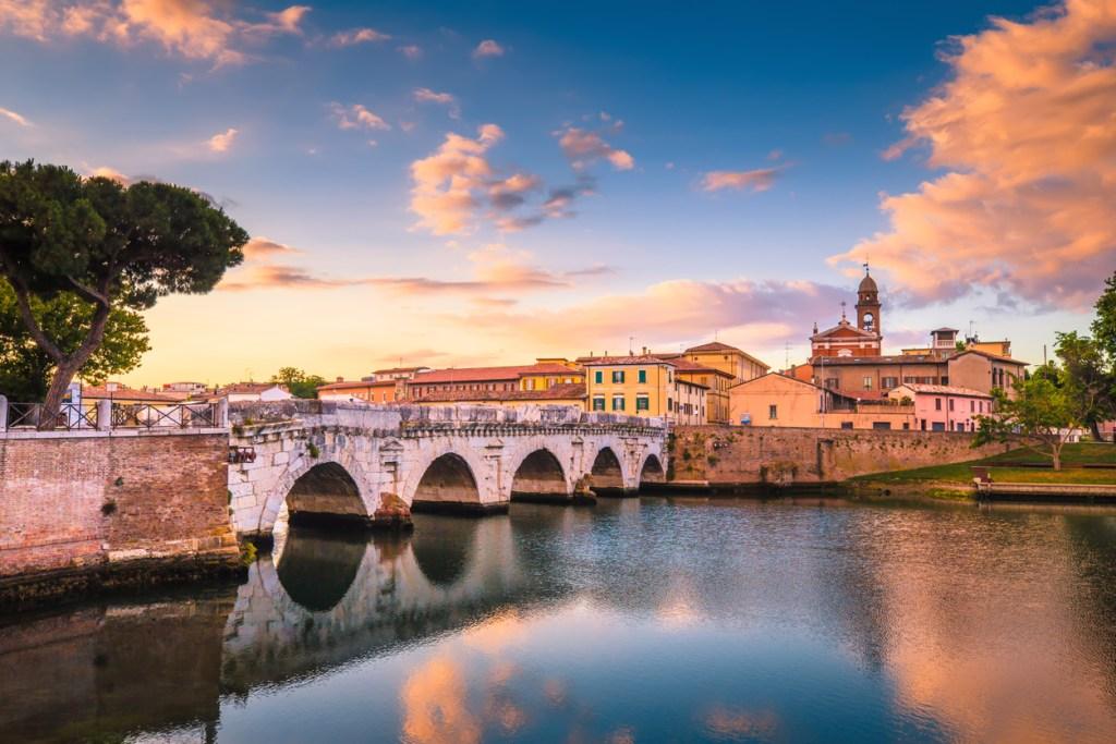 Rimini cityscape. Tiberius bridge famous sightseeing in Rimini at dawn. Summer sunrise in Rimini historic center.
