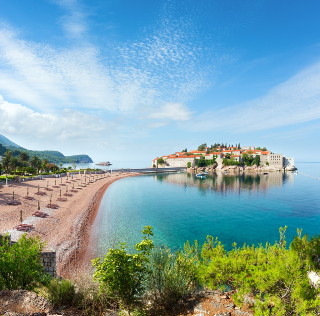 The view of Sveti Stefan sea islet with pink sandy Milocer Beach