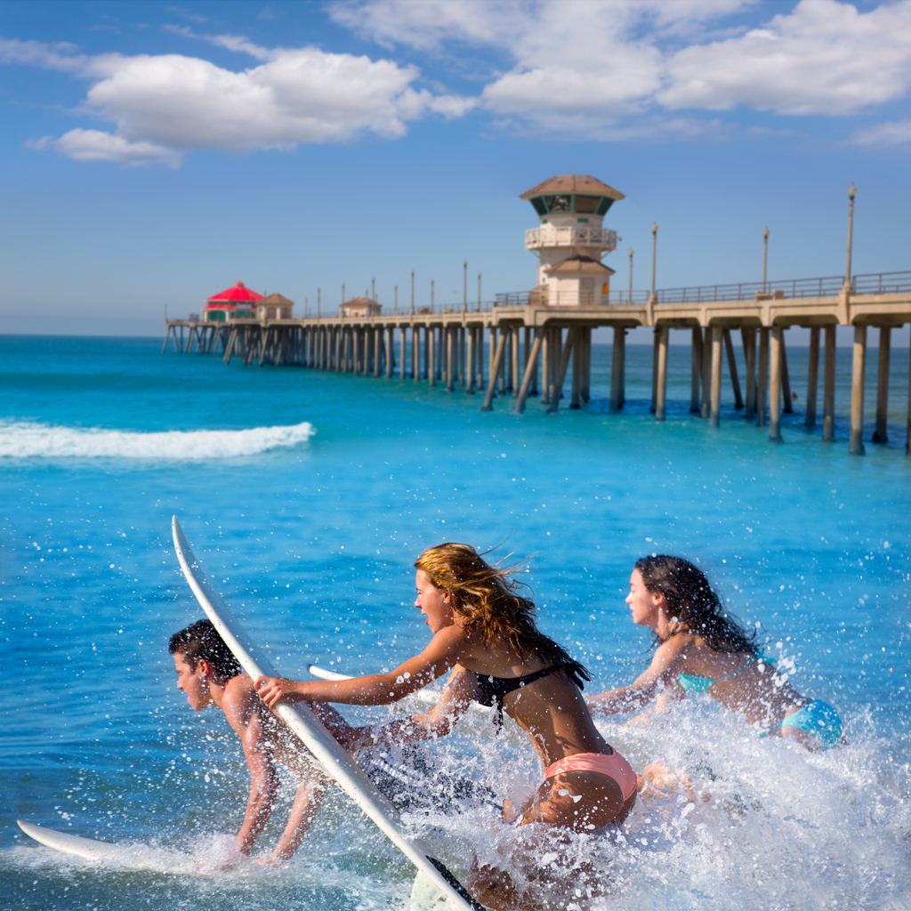 Teenager surfers surfing running jumping on surfboards at Huntington beach pier California