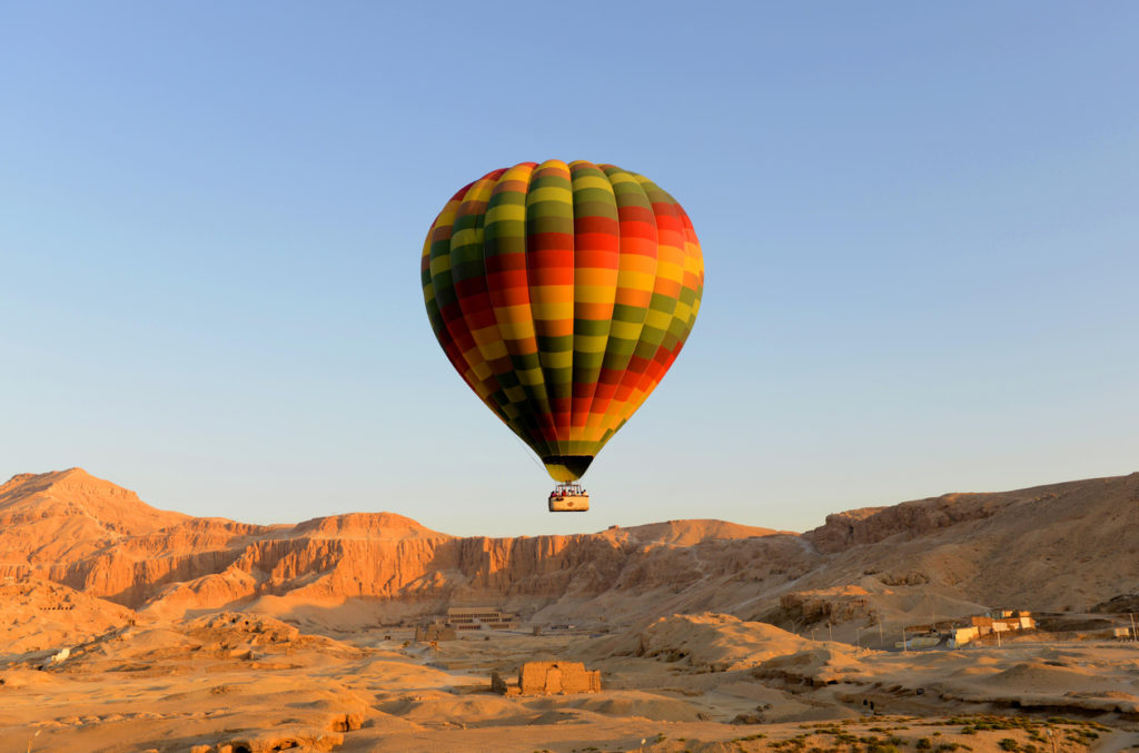 Hot air balloon lifting off in Luxor, Egypt with the temple of Hatshepsut in background