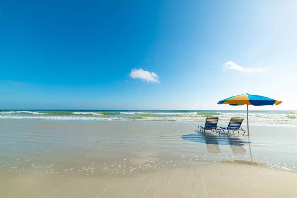 Parasol and beach chairs on the foreshore in Daytona Beach. Florida, USA