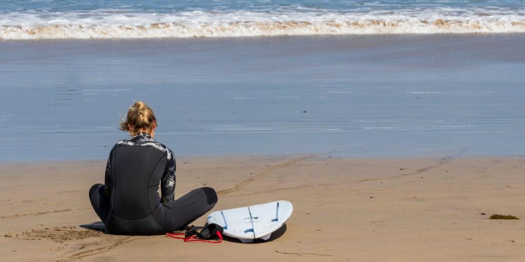 Surfer girl sitting at La Caleta beach. Lanzarote.