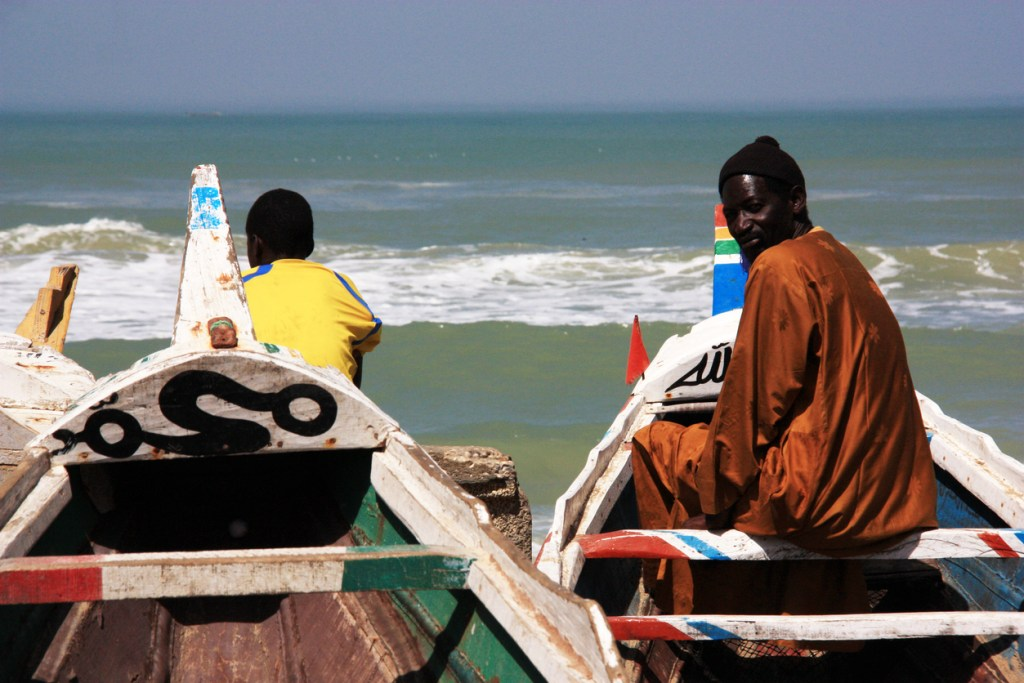 Fishermen sitting in their colorful painted pirogues in Saint-Louis-du-Sénégal