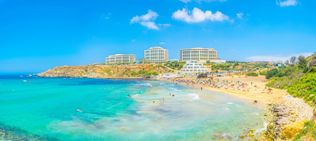 People are enjoying a sunny day at the Golden Bay beach on Malta