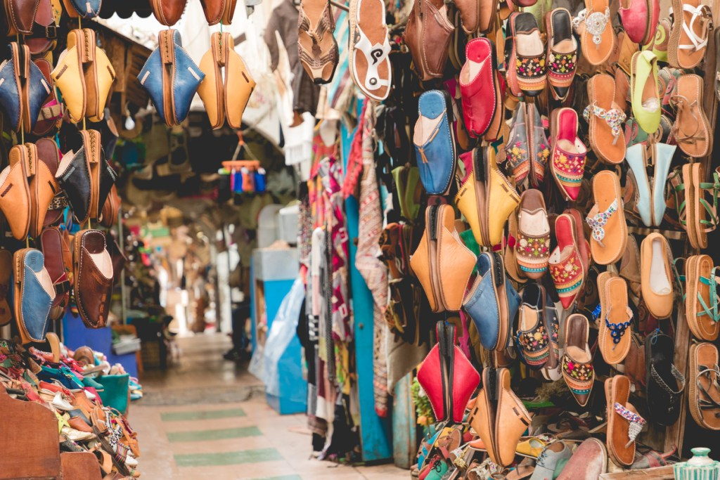 Moroccan leather goods bags and slippers at outdoor market in Marrakesh