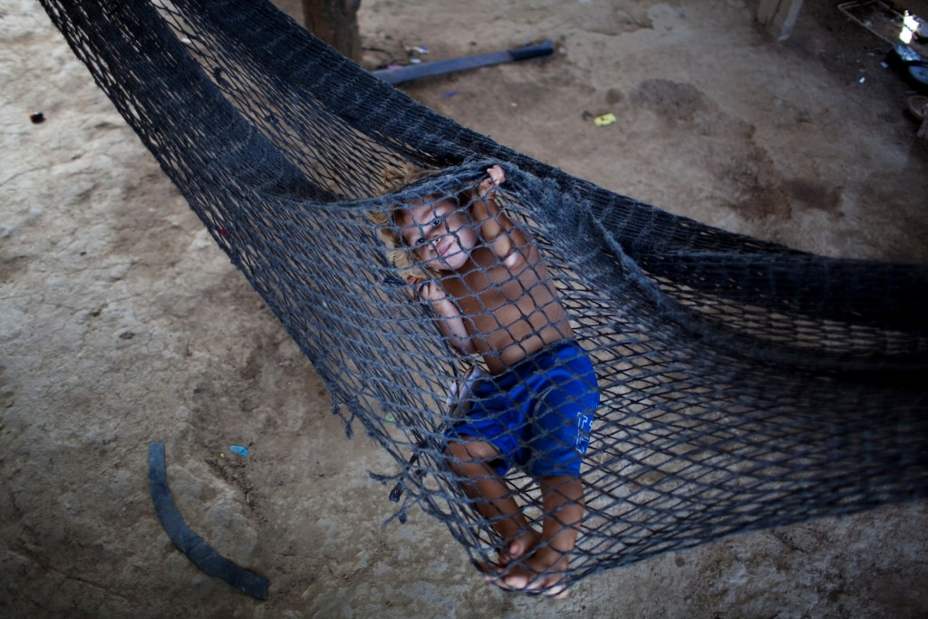 "In this May 5, 2012 photo, Gerson Sarai Melgar, 3, rests in a hammock inside his house in ""La Confianza"" peasant model city, Bajo Aguan, Honduras. Peasants from MUCA (Movimiento Unificado Campesino del Bajo Aguan) occupied around 7000 sq meters of productive land close to the city of Tocoa in the Valley of Bajo Aguan, eastern coast of Honduras in December, 2009. They operate a comercial production of african palm and they also stablished what they call a ""peasant model city"" called ""La Confianza"" where more than 300 hundred families live. Since then an open conflict between them and the alleged owner of the land, Miguel Facussé, one of the most powerful businessmen in Honduras has left more than 60 people dead including peasants, security guards, a journalist and members of the Honduran national police. (AP Photo/Rodrigo Abd)"